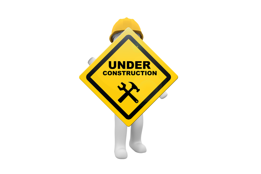 "A man wearing a yellow hardhat holding an ""Under Construction"" sign"