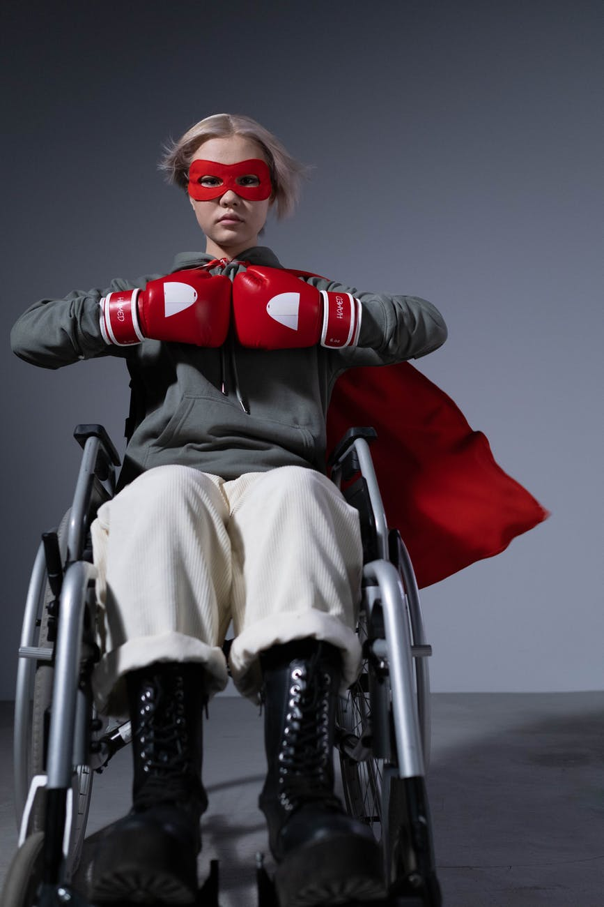 young woman in wheelchair wearing a superhero mask, a cape, and boxing gloves. Badass.