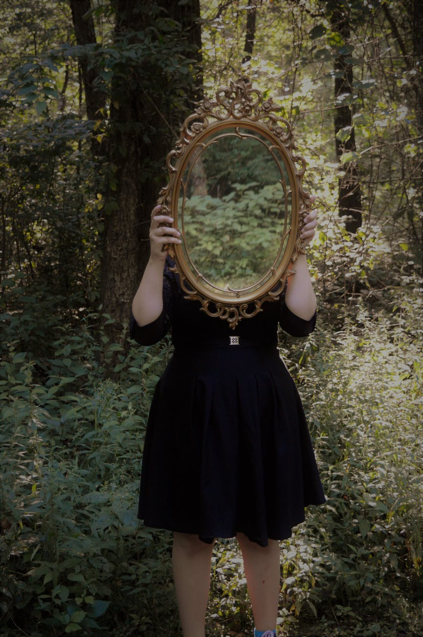 person wearing a black dress holding a mirror in the woods
