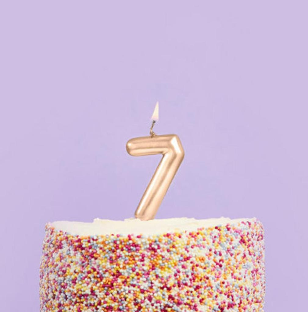 Candle shaped like the number 7 burning atop a sprinkled cake