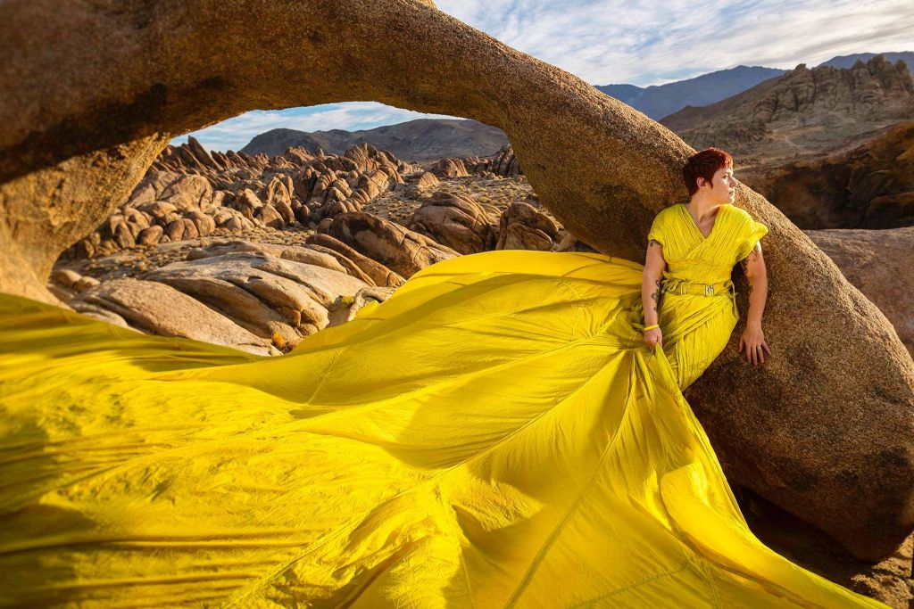 woman in a long yellow gown standing against a rock arch near Lone Pine, CA